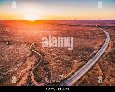 Orange sunset over dry land and rural highway winding through in South Australia - Stock Photo