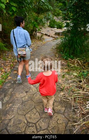 Mother and daughter walk down the track from Panjoo lookout, Cardwell, Queensland, Australia - Stock Photo