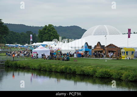 Large crowd of people at showground, many sitting by refreshment trade stands & marquee at busy RHS Chatsworth Flower Show, Derbyshire, England, UK. - Stock Photo
