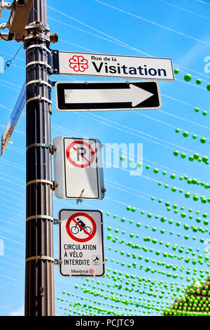 Rue de la visitation, no parking and no bicycle riding  street signs and the green balls of gay village in Montreal, Canada - Stock Photo