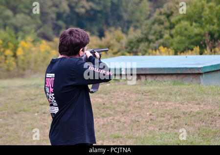 A young man taking aim on the line trap shooting at the Collier's Sportsman club in Collier, PA, USA - Stock Photo