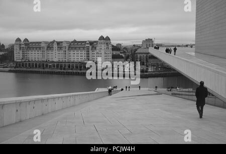 A man walking on the roof top of Oslo Opera House - Stock Photo