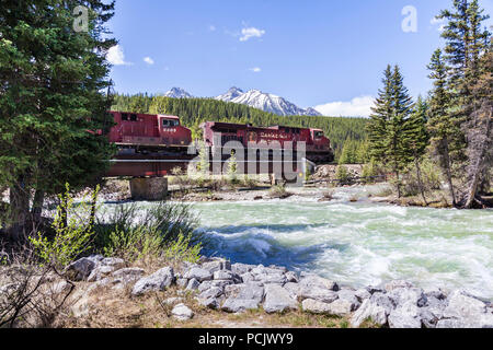 A freight train on the Canadian Pacific Railway crossing the Bow River in the Rocky Mountains at the town of Lake Louise, Alberta, Canada - Stock Photo
