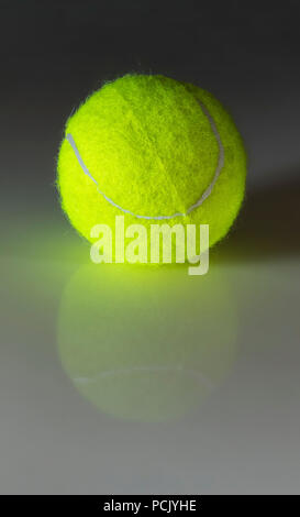 A bright green tennis ball on a smooth white reflection surface close-up. - Stock Photo