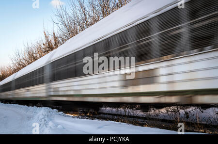 The freight train rushes along the railway tracks. - Stock Photo