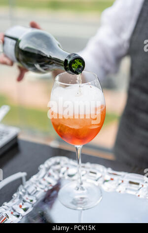 Bartender makes cocktail Aperol spritz. Misted glass, selective focus. Alcoholic beverage based on bar counter with ice cubes and oranges. outdoor party