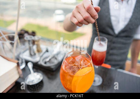 Bartender makes cocktail Aperol spritz. Misted glass, selective focus. Alcoholic beverage based on bar counter with ice cubes and oranges. outdoor party - Stock Photo
