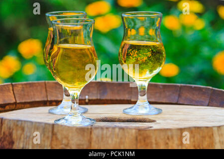 glasses with cider stand on a barrel with yellow flowers in the background, summer holidays - Stock Photo