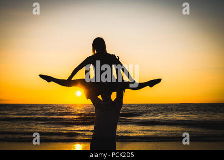 Silhouettes of two dancers doing acrobatics at sunset near the beach at the seaside - Stock Photo