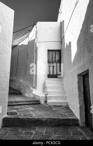 This is a black and whit photo of a narrow step path that go through the village of Lindos in Rhodes - Stock Photo