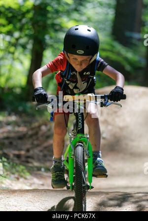 A young boy (6 yr old) riding his bike looking straight at the camera, Kingdom Trails, East Burke, Vermont, USA - Stock Photo