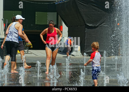 People keeping cool in the water fountains in Montreal in the 2018 heatwave - Stock Photo