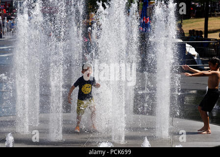 Children cooling off playing in water fountains in on Rue Jeanne Mance in Montreals Entertainment District. Taken during the 2108 heatwave. - Stock Photo