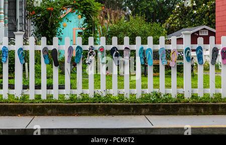 Assateague, VA, June 23, 2018, fence decorated with flip flops - Stock Photo