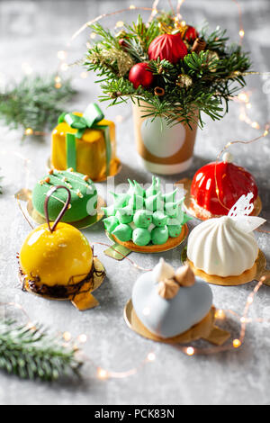 Merry Christmas card. Variety of sweet delicious cakes. Fir branches on a gray background. Merry Christmas card. New year mood - Stock Photo