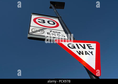 british road signs indicating give way and the start of a 30mph speed limit and the end of a 20mph speed limit zone