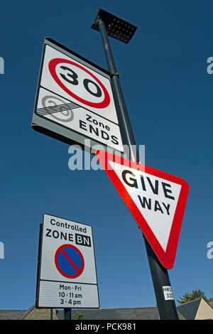 british road signs indicating give way, the start of a 30mph speed limit and the end of a 20mph speed limit zone, with controlled parking sign to rear