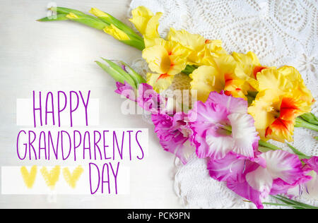 Beautiful gladiolus on wooden background. Bouquet of colored gladioli. Happy grandparents day. - Stock Photo