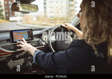 Female executive using navigation while driving a car - Stock Photo