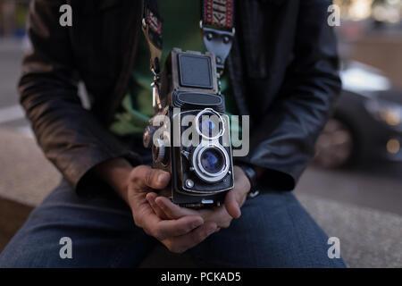 Photographer with camera sitting on surrounding wall near street - Stock Photo