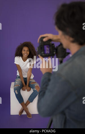 Photographer taking picture of model in studio - Stock Photo