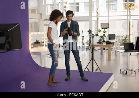 Photographer showing photos to fashion model on digital camera - Stock Photo