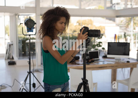 Photographer taking pictures in the studio - Stock Photo
