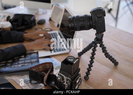 Photographer using laptop on desk - Stock Photo