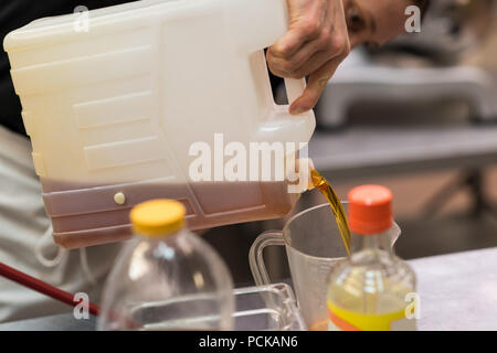 Chef pouring edible oil in a container - Stock Photo
