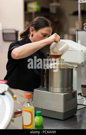 Chef pouring edible oil in a grinder - Stock Photo
