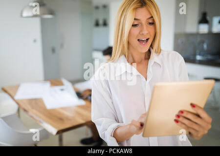 Attractive woman working on a tablet in a home office. - Stock Photo