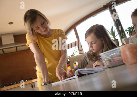 Mother helping children with homework in kitchen - Stock Photo