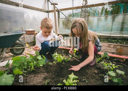 Kids gardening in greenhouse