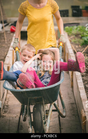 Mother having fun with kids in wheelbarrow - Stock Photo