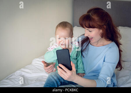 Mother and baby girl taking selfie with mobile phone in bedroom - Stock Photo