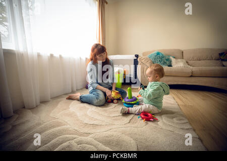 Mother with her baby girl playing with toys - Stock Photo