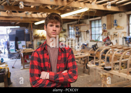 Male carpenter standing with arms crossed - Stock Photo