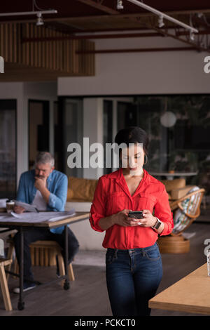 Office executive using mobile phone at creative office - Stock Photo