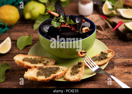Boiled mussels in cooking dish on wooden background - Stock Photo
