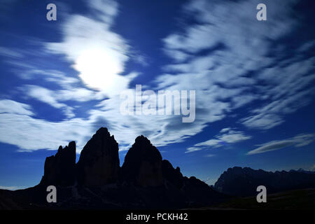 North walls of the Three Peaks of Lavaredo at full moon night, Sexten Dolomites, Hochpustertal valley, South Tyrol, Italy - Stock Photo