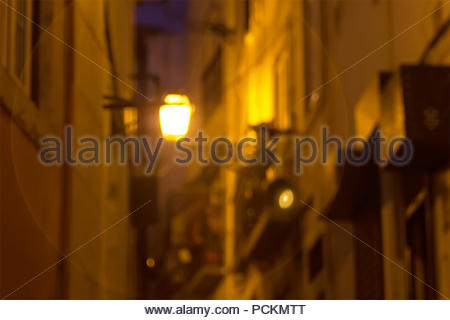 The lantern shines at night on a small street. Lisbon, Portugal - Stock Photo