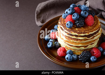 Stack of pancakes with fresh blueberry, raspberry and blackberry on brown plate - Stock Photo