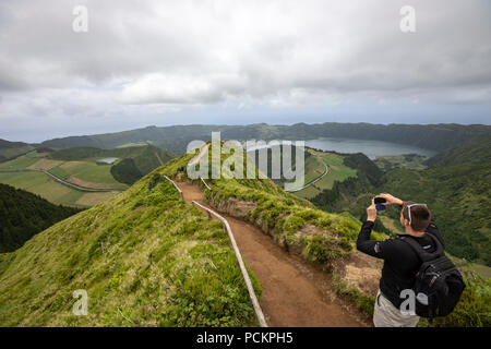 Tourist taking picture in a path to Lagoa do Canario Miradouro, viewpoint, and Santiago Lake and part of Sete Cidades Lake. Sao Miguel island, Azores - Stock Photo