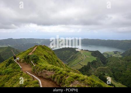 Tourists on a path leading to Lagoa do Canario Miradouro, viewpoint, taking pictures over Sete Cidades Lake. Sao Miguel island, Azores. - Stock Photo