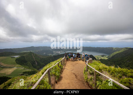 Tourists on Lagoa do Canario Miradouro, viewpoint, and Santiago Lake and part of Sete Cidades Lake. Sao Miguel island, Azores. - Stock Photo