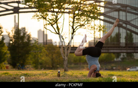a young woman doing a splits handstand on the grass in a