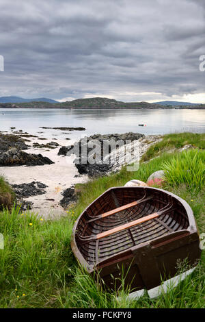 Sand beach and rocky shore of Isle of Iona with beached boat and view of Fionnphort Isle of Mull Sound of Iona Inner Hebrides Scotland UK - Stock Photo