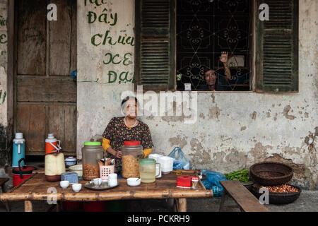 Duong Lam, Ha Noi, Vietnam-April 18, 2018: Vietnamese woman vendors in the street market of the ancient city Duong lam. - Stock Photo