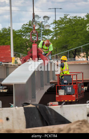 Detroit, Michigan - Workers set a girder in place while rebuilding a bridge on Interstate 94. - Stock Photo