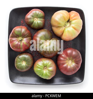 Organic heirloom tomatoes on a black square plate, isolated on white, top view - Stock Photo